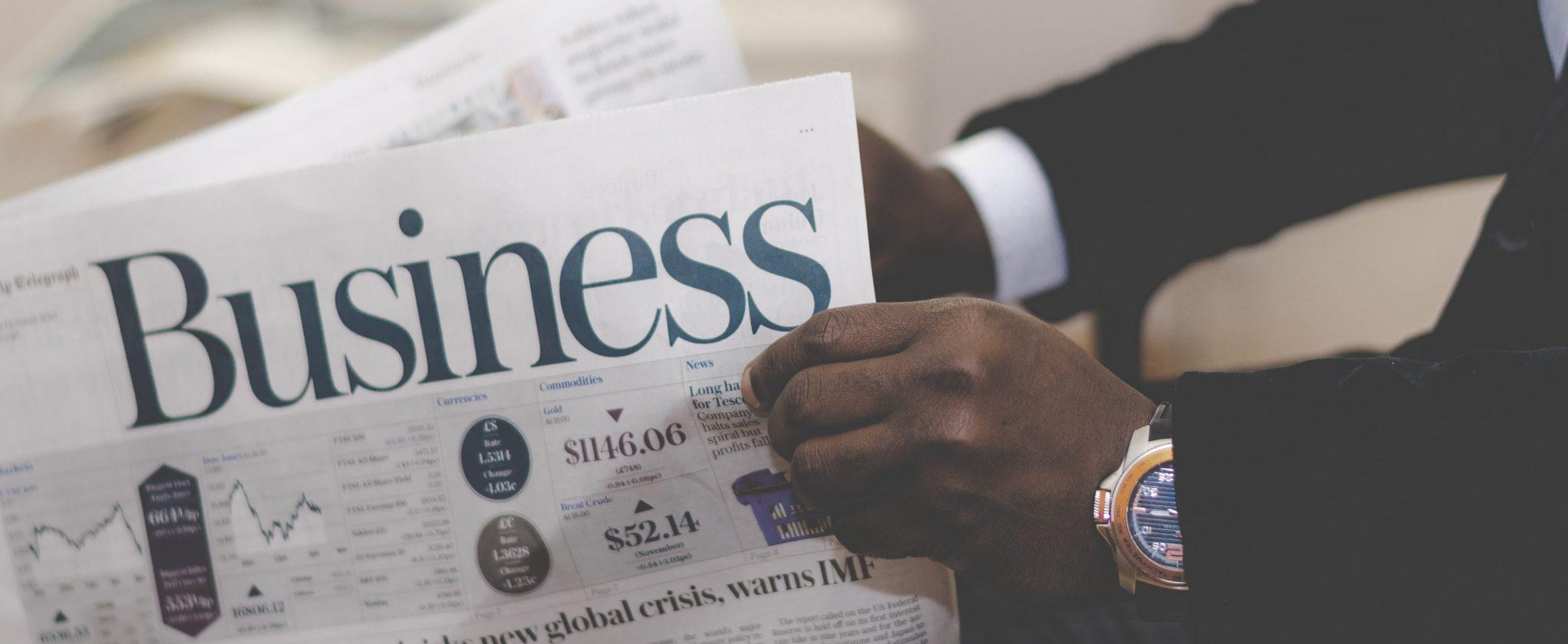 Eine Business-Zeitung wird von einem Investor mit Uhr gelesen.