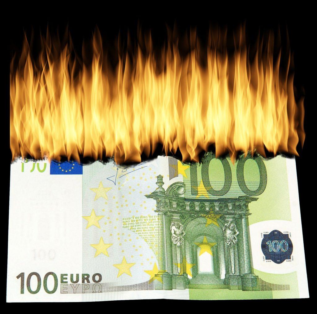 Geld brennt im Feuer einer Finanzkrise mit Inflation.
