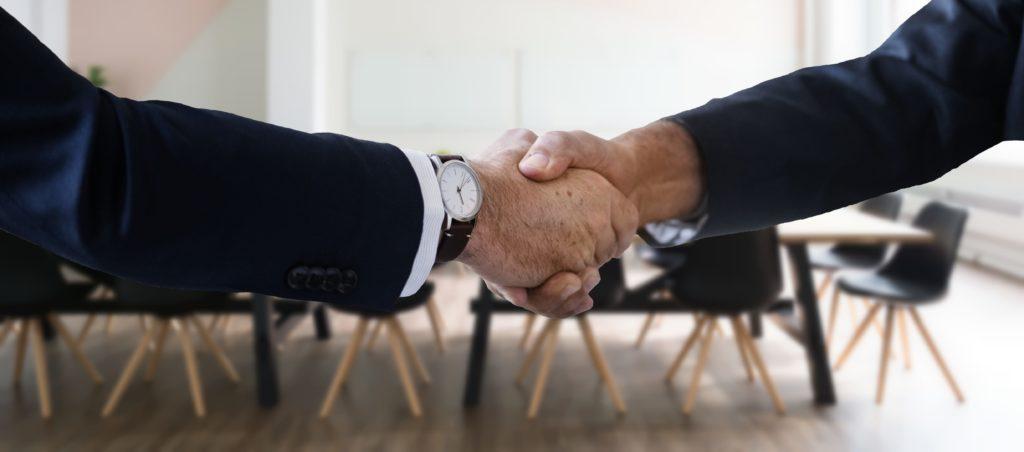 Zwei Hände werden vor einer Stuhlreihe geschüttelt und besiegeln gute Zusammenarbeit.