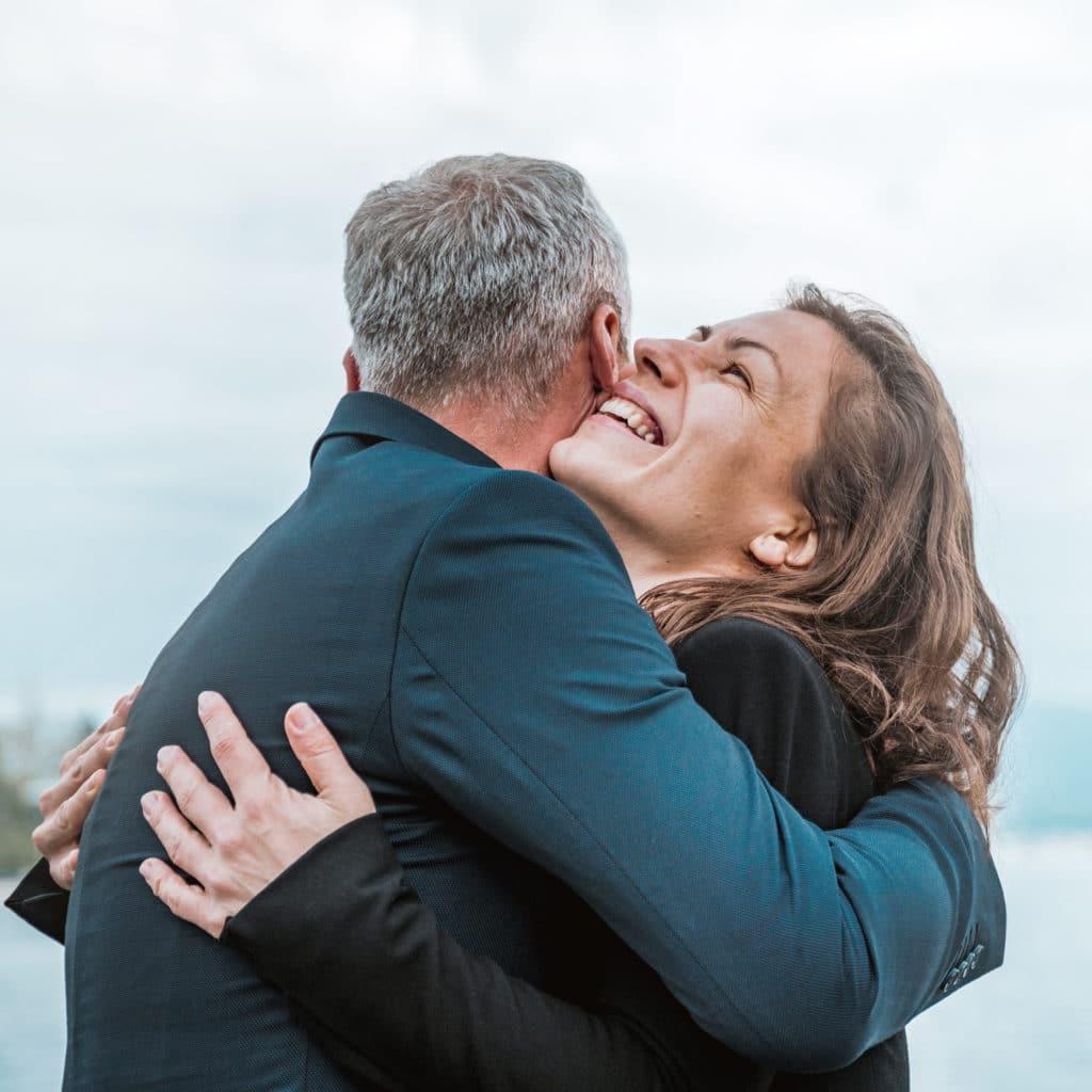 Das Bild zeigt, wie eine Frau einem Mann vor Freude um den Hals fällt