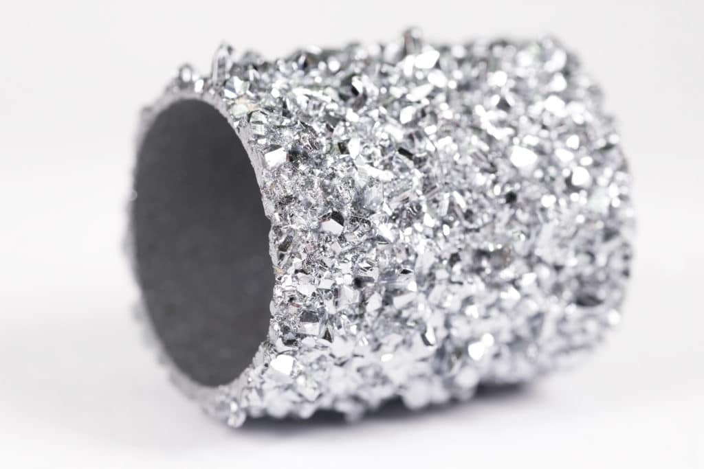 Osmium besitzt eine kristalline Oberfläche, die in einer gebogenen Form als Rundbarren für einen Osmium-Ring als Rohmaterial dient.