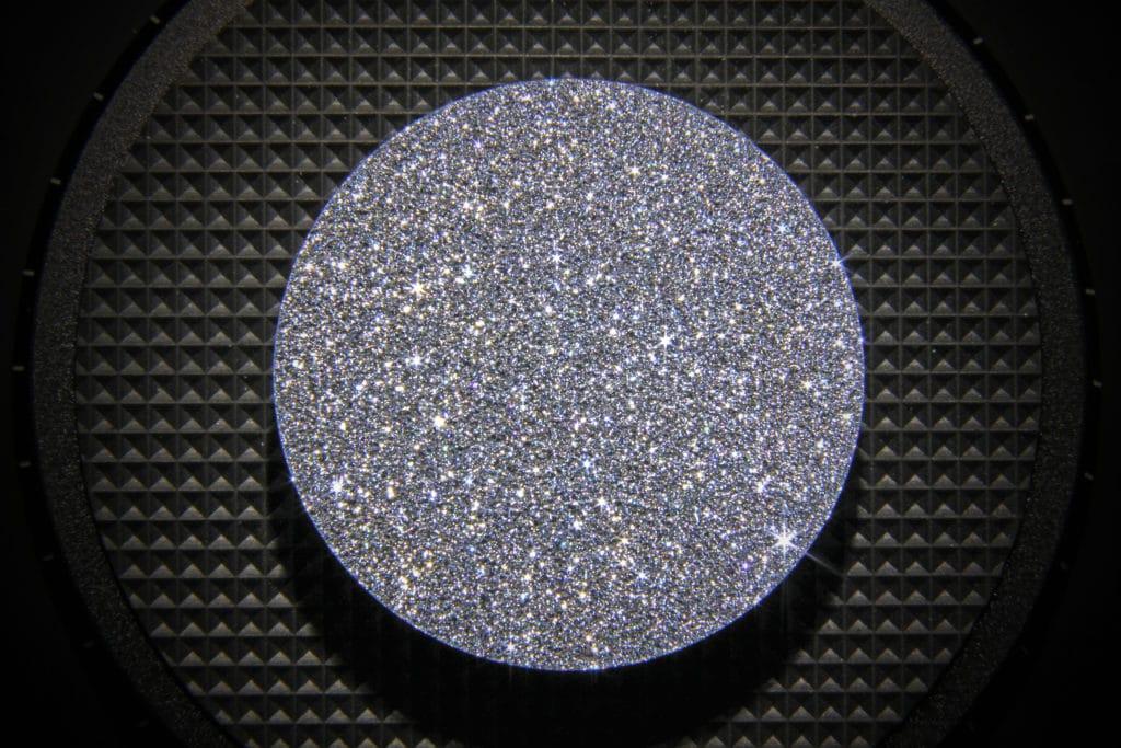 Eine Osmium-Disk reflektiert das Licht und der Sparkle des kristallinen Edelmetalls entsteht