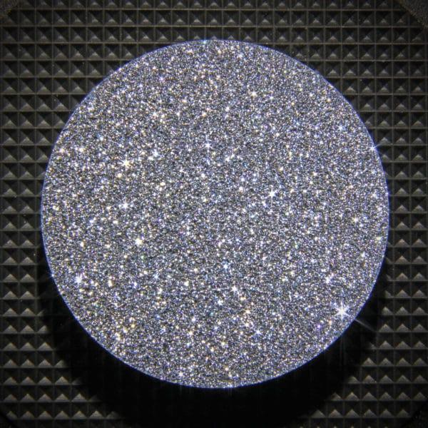 Funkelnde Osmium Disk vor dunklem Hintergrund.