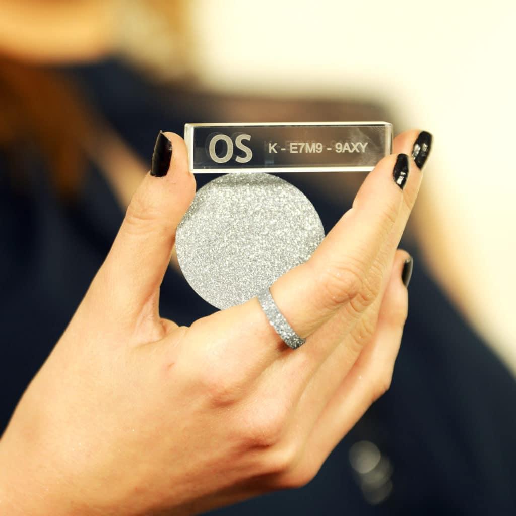 Ein Osmium-Rundbarren am Finger, eine Osmium-Disk in der Hand und der mitgelieferte Glasbarren werden auf einem Bild gezeigt