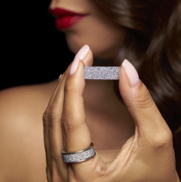 Der Osmium-Ring wird von einer Kundin getragen und ein Barren aus dem Edelmetall gehalten