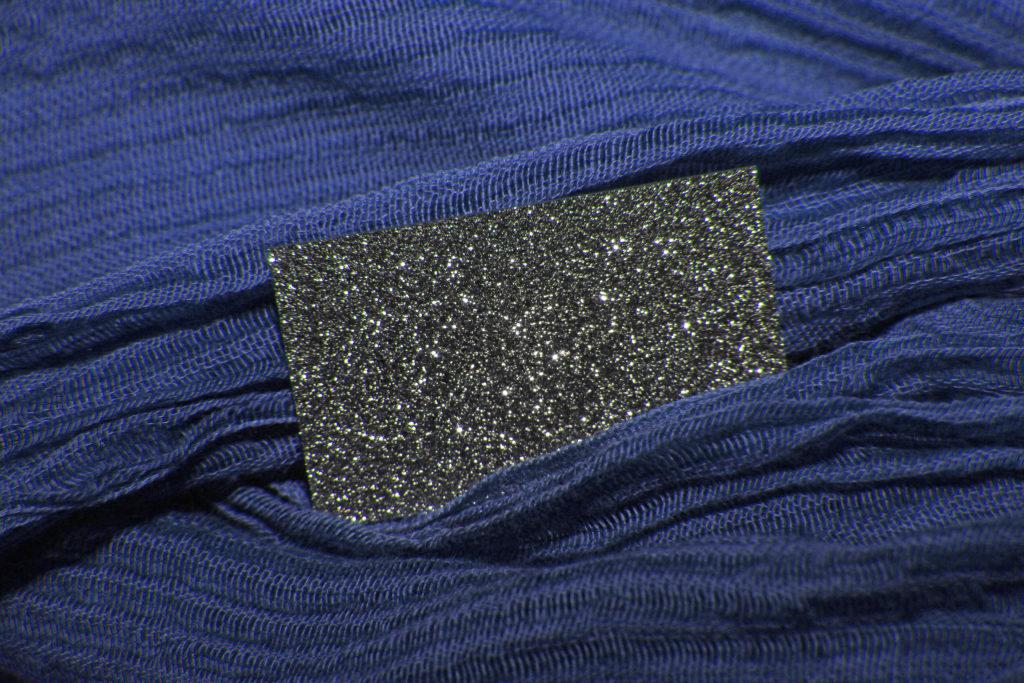 Ein Barren aus Osmium funkelt edel im Kontrast mit blauem Stoff.