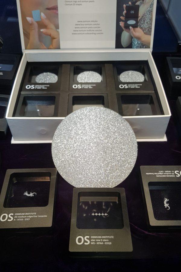 Eine Disk aus Osmium befindet sich in der Mitte von mehreren Osmium-Produkten in ihren Sichtboxen