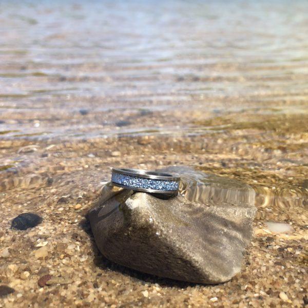 Osmium Produkt Schmuck Ring am Wasser am Strand