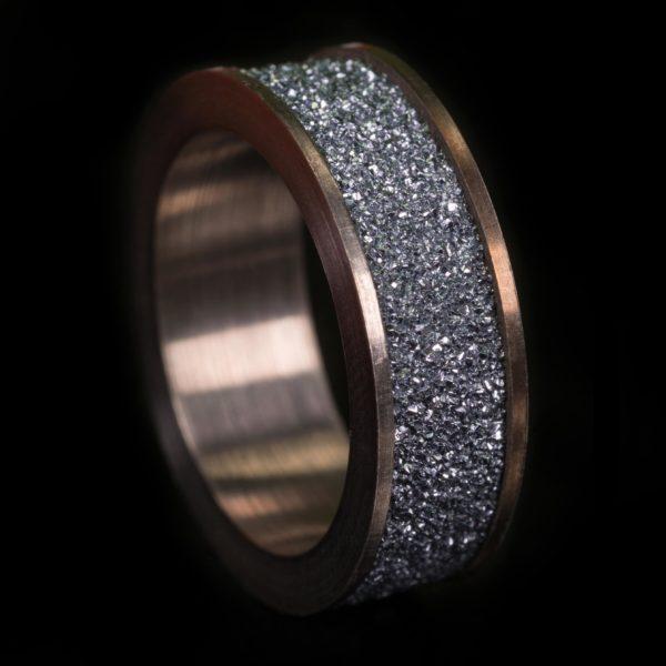 Osmium Produkt und Schmuckstück in Form eines breiten Damenringes steht aufrecht