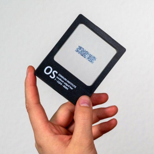 Eine Hand hält das Produkt Osmium-Barren in der Sichtbox
