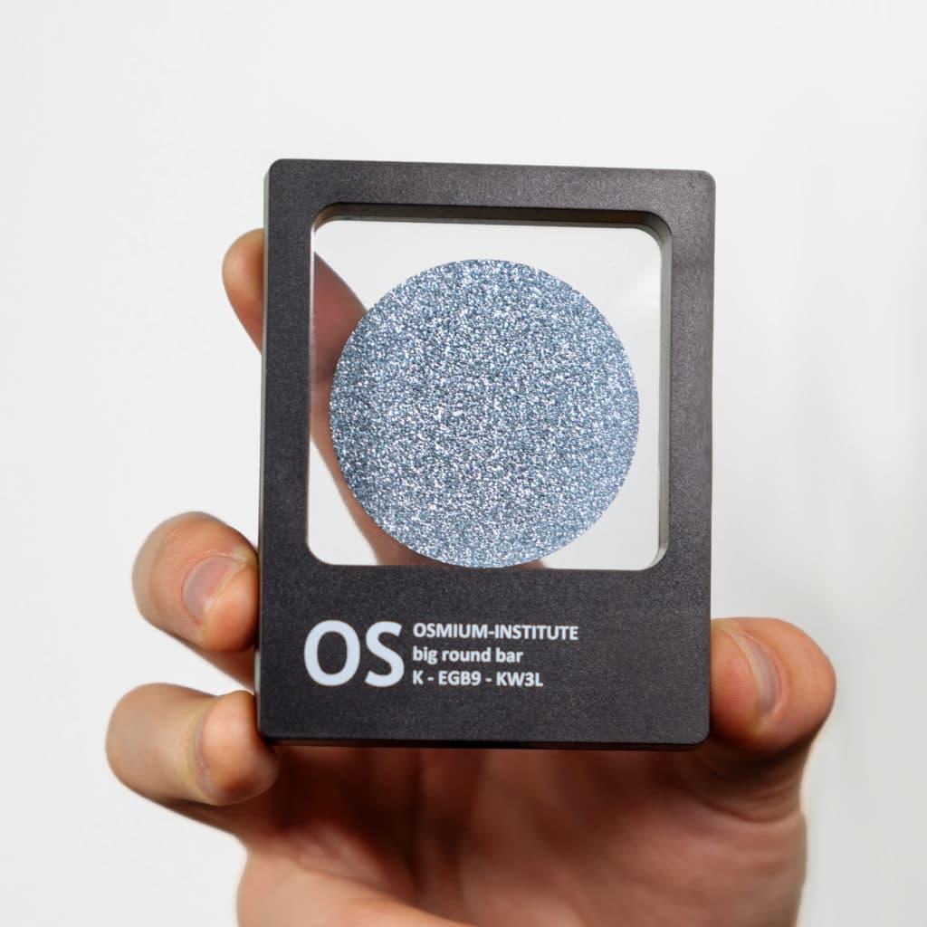 Eine Hand hält das Produkt Osmium-Disk in der Sichtbox