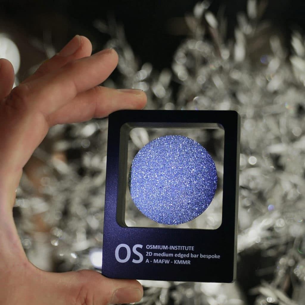 Eine Hand hält das leuchtende Produkt Osmium-Disk in der Sichtbox