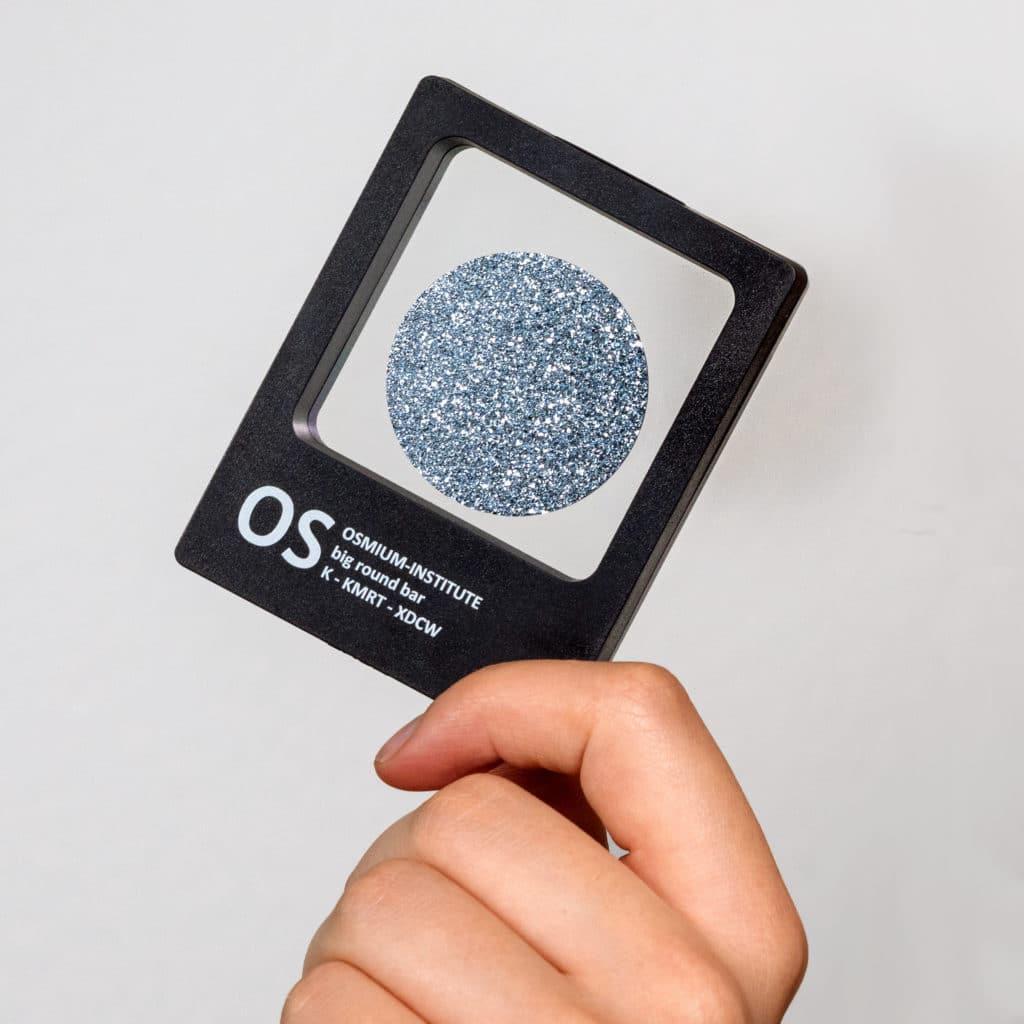 Eine Hand hält diagonal das Produkt Osmium-Disk in der Sichtbox