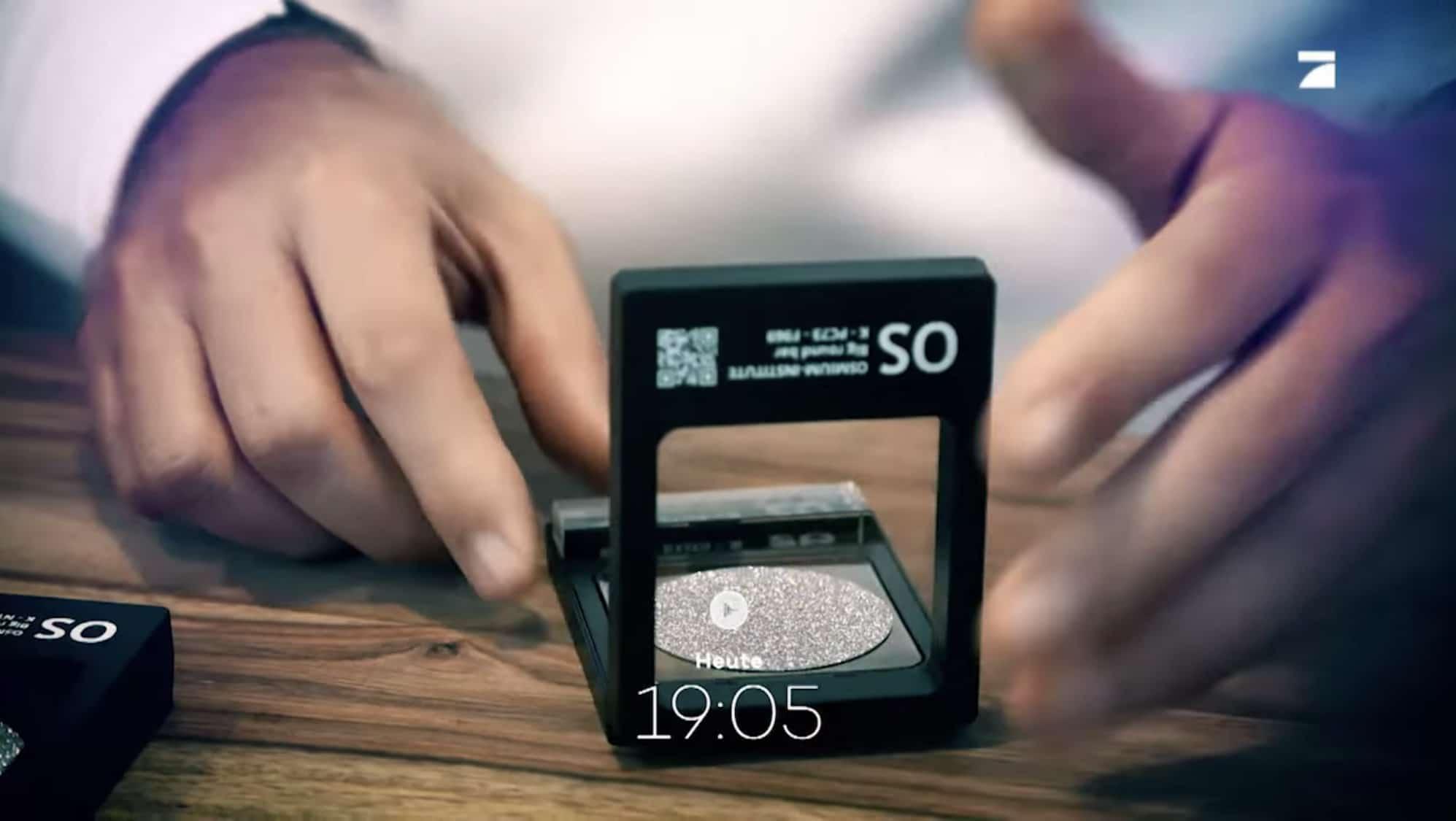 Ein Interessent öffnet eine Osmium-Sichtbox und holt die wertvolle Edelmetall-Disk heraus.