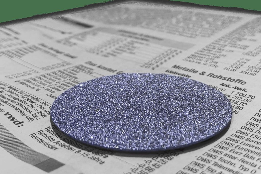 Eine Osmium-Disk liegt auf dem Rohstoff- und Ressourcenteil einer Wirtschaftszeitung